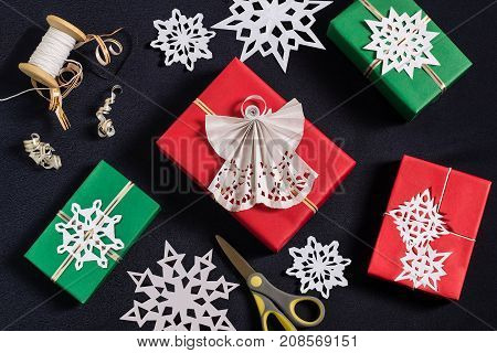 Decoration of gift boxes for Christmas with your own hands. DIY hobby. Boxes are wrapped in red and green paper tied with ribbons with handmade snowflakes and angel. Original gift decoration
