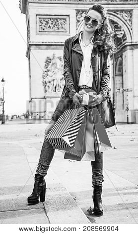 Stylish Christmas in Paris. Full length portrait of happy young woman in sunglasses with shopping bags and Christmas present near Arc de Triomphe in Paris France