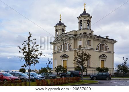 Orthodox Church with two towers with bells and crosses on the background of the cloudy sky on a cloudy day.