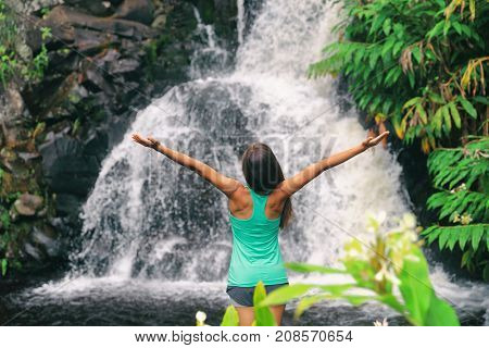 Hawaii travel nature waterfall woman hiker at Canyon Trail Waipoo Falls in Waimea, Kauai island, USA. Freedom happy girl with open arms meditating yoga in rainforest.