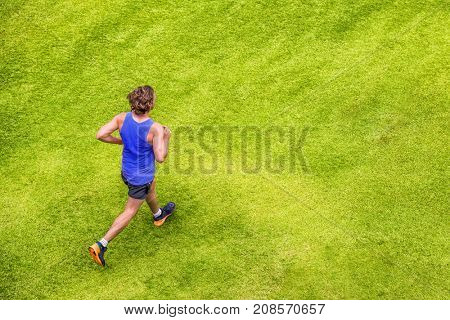 Runner man running jogging on summer green grass texture park jogging healthy lifestyle. People working out cardio top view. Copy space on background.