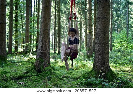Women is suspended in the forest. Hanging in the forest, holding on strings, not touching the floor