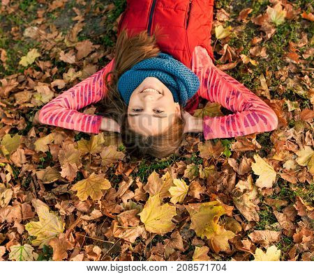 Smiling young girl lying down on autumn maple leaves at fall outdoors. Portrait of a beautiful smiling teenage. Young teenager girl looking to camera. Autumn winter season.