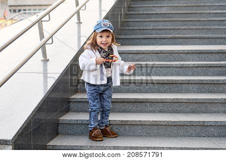 model child hip-hop.girl child street fashion jeans clothes.Model child hip - hop is standing on the stairs outdoors.Portrait of a cute little girl in fashionable denim clothes.beautiful child.