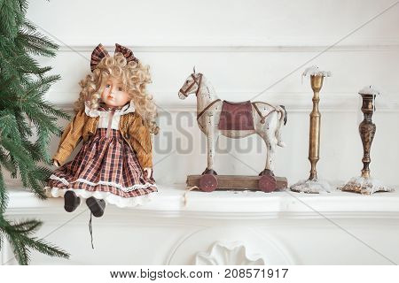 Vintage dollwooden horse on wheels and candlesticks on the cornice of decorative fireplace. Christmas tree decor.