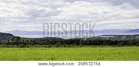 Wide view of farm fields leading down to the Saint Lawrence Seaway and the low mountains beyond near Riviere du Loup, Quebec on a bright sunny day with blue skies and clouds in August.