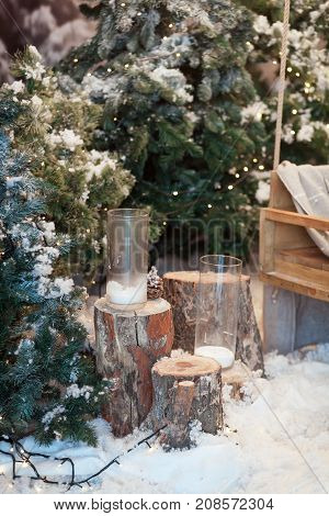 Beautiful Christmas interior design. Close-up of decorated snow-covered Christmas tree with stumps, candles in glasses. Concept of Merry Christmas, winter and New Year.