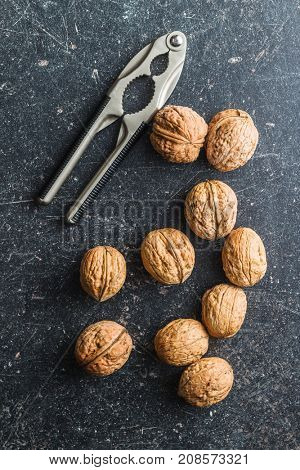 Tasty dried walnuts with nutcracker. Top view.