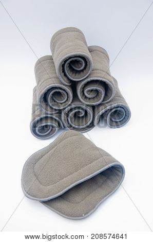 Stack of grey bamboo microfiber inserts to baby reusable diapers lay on white background