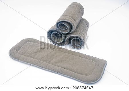 Three grey rolled and one deployed microfiber cloth inserts to baby reusable cotton diapers on white background