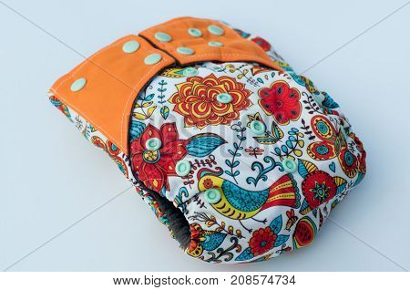 Cotton reusable baby diaper with buttons and pattern lay on white background