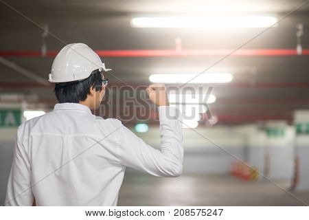 Young Asian engineer or architect man holds up fist in the air at construction site success after finished job concept