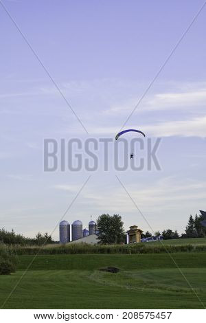 Saint Quentin, New Brunswick - August 17, 2011 - Vertical of a man sitting on a motorized fan seat attached to a para-sail flying through the blue sky with a farm with silos in the background near Bathurst, NB, on a bright sunny day