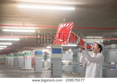 Young Asian engineer man wearing safety helmet yelling though traffic safety cone in parking lot. Construction cone safety concept