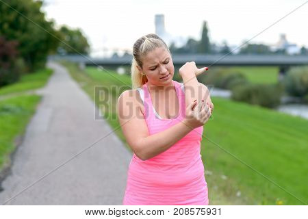 Young Blonde Woman Holding Her Painful Elbow