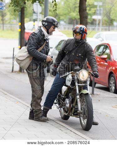 STOCKHOLM SWEDEN - SEPT 02 2017: Two senior motor cyclist wearing leather jacket talking at the Saint Eriks bridge Stockholm Sweden September 02 2017