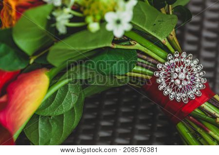 A silver brooch with rhinestones on the stalk of the wedding bouquet with red ribbons. Close-up. Artwork. Copy space