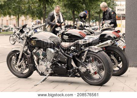 STOCKHOLM SWEDEN - SEPT 02 2017: Parked black retro motorcycles at the Mods vs Rockers event at the Saint Eriks bridge Stockholm Sweden September 02 2017