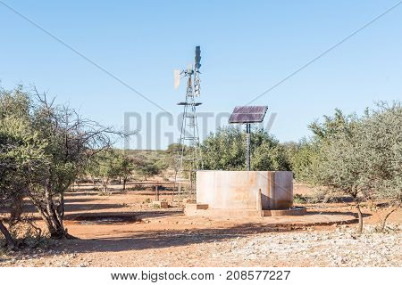 A water-pumping windmill and solar panels for a waterpump near Schmidtsfrift a village in the Northern Cape Province of South Africa