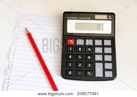 A Studio Photograph Showing A Calculator Pencil & Notepaper