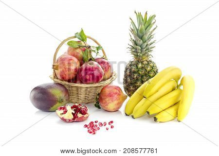 Mango, pineapple, bananas, garnet  on white background closeup
