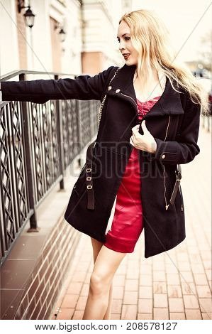 Beautiful fashion woman walking in the street of city. Wearing short black coat and red dress