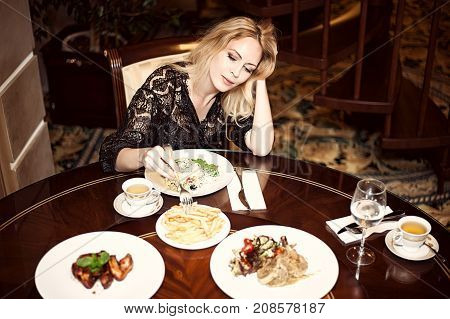 Beautiful woman eating in a dining room. Breakfast dinner or lunch