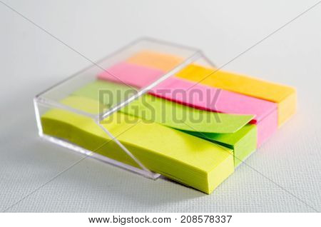 A Studio Photograph of Fluorescent Sticky Notes Housed Within a Plastic Holder