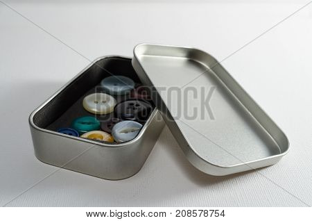 A Studio Photograph of a Metal Tin Constaining Assorted Buttons