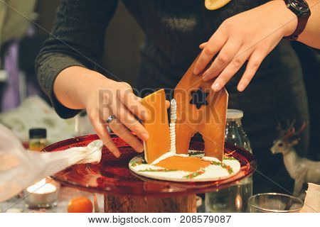 Gingerbread house making by hands. Sweet course for Christmas holiday.handicraft before Xmas party. Use for recipe and master class. Teaching to cook
