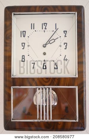 Soviet wall brown simple clock with pendulum is on white wall
