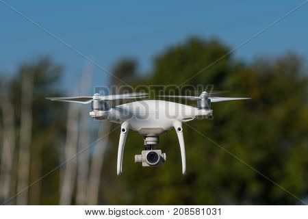Moscow, Russia - 24 September, 2017: A Phantom 4 Pro Drone In Flight, Green Trees In The Background,