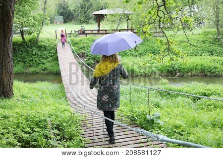 Woman and girl go on hanging bridge over small river in green forest