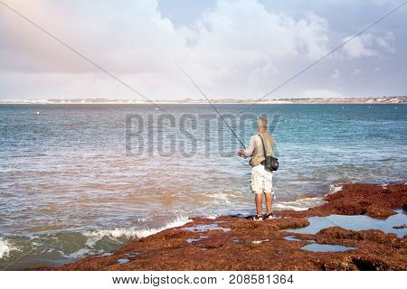 a fisherman catches a fish on a stone beach