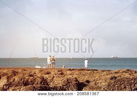 fishermen catch fish on the stone beach