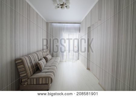 Empty simple cozy room with balcony door, striped walls and striped sofa