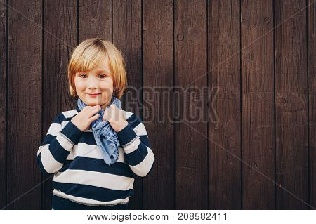fashion portrait of adorable little boy of 4-5 years old wearing stripes blue and white sweatshirt