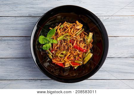 Traditional Chinese dish on a round black plate, rice noodles, cabbage green cabbage and fried vegetables. On a wooden gray table. Close-up. View from above.