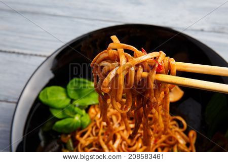 Traditional Chinese dish on a round black plate, rice noodles, cabbage green cabbage and fried vegetables. Chinese chopsticks. On a wooden gray table. Close-up. View from above.