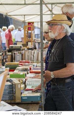 DORDRECHT NETHERLANDS - JULY 7 2013: People standing at a second hand book stall at the annual book market held in the old centre of Dordrecht. The market attracts 75000 visitors annually.