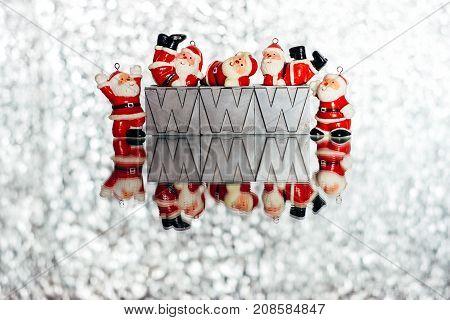 Small Santa's decorations on sparkling silver shiny background with W,w,w.