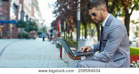 Businessman texting on laptop seated on brench on street