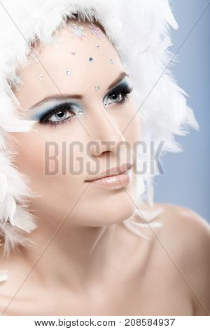 Closeup portrait of glamorous winter beauty in professional makeup and white feather cap.