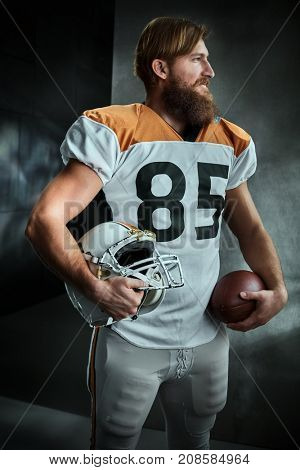 Portrait of bearded american football player in jersey standing holding helmet and ball.