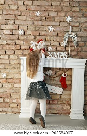 Little girl playing with decorations on fireplace at christmas time, tiptoing.