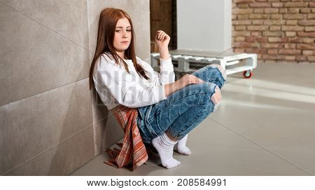 Young ginger-haired girl squatting by wall at home.