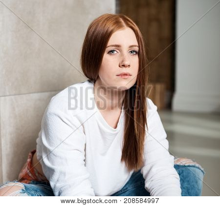 Portrait of young ginger-haired girl looking at camera.