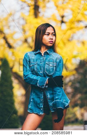 Fashionable young woman wearing blue jeans jacket with the high hills and long stripe knee socks. outumn fashion style