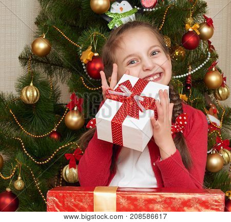 Girl near christmas tree and gift boxes, happy holiday and winter celebration, dressed in red