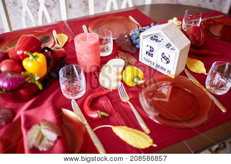 A beautiful festive table served with a red tablecloth. Different vegetables, glasses, plates, napkins for holidays table. Close-up of objects. Food concept.